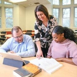 3 people at a table looking at a book