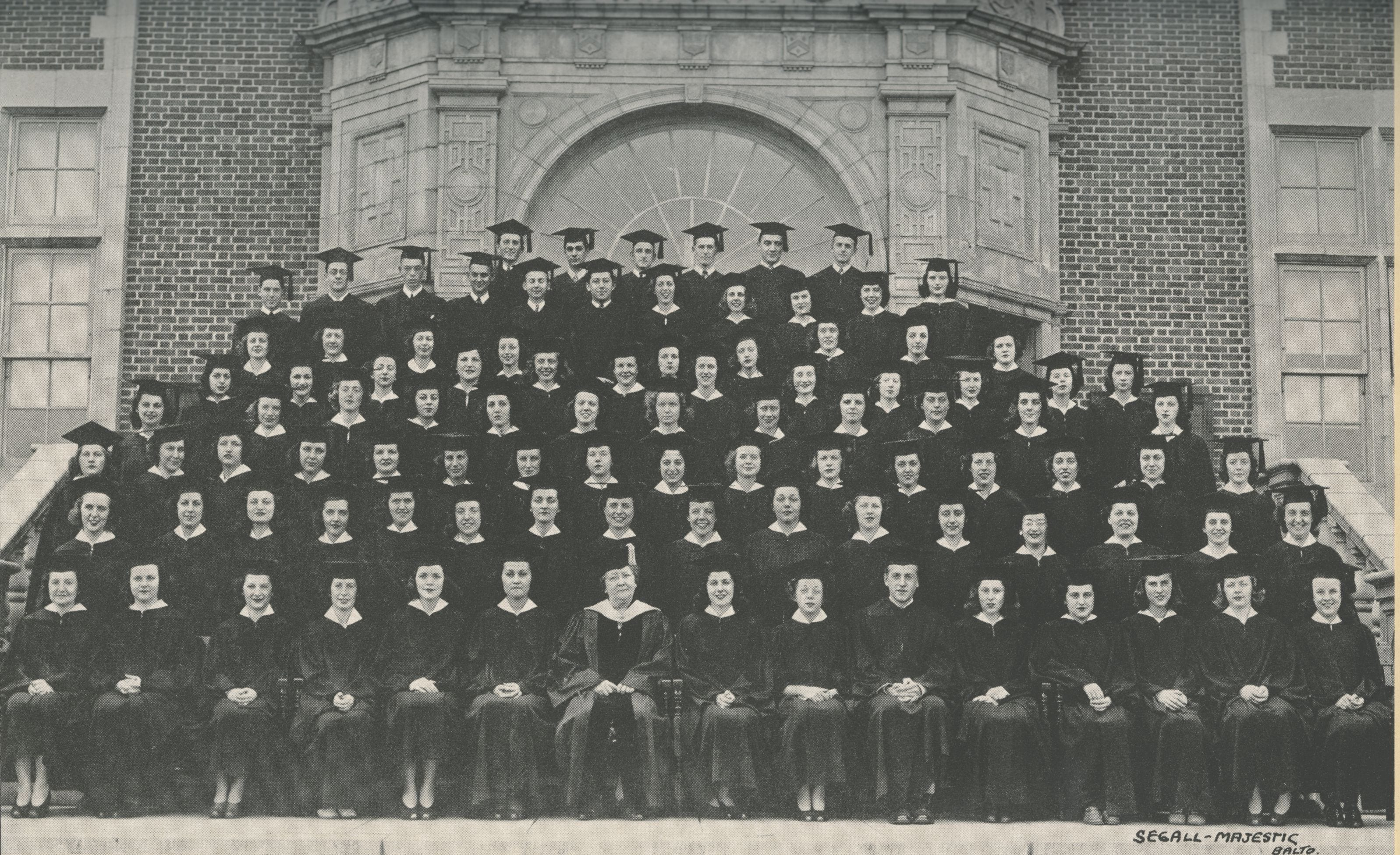 Photo of graduates in caps and gowns arranged on steps in front of Stephens Hall. Dr. Wiedefeld is seated in front and center of the photo dressed in academic regalia