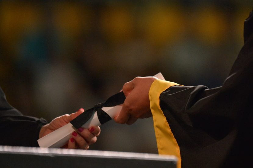 Photograph of one person handing another a rolled diploma.