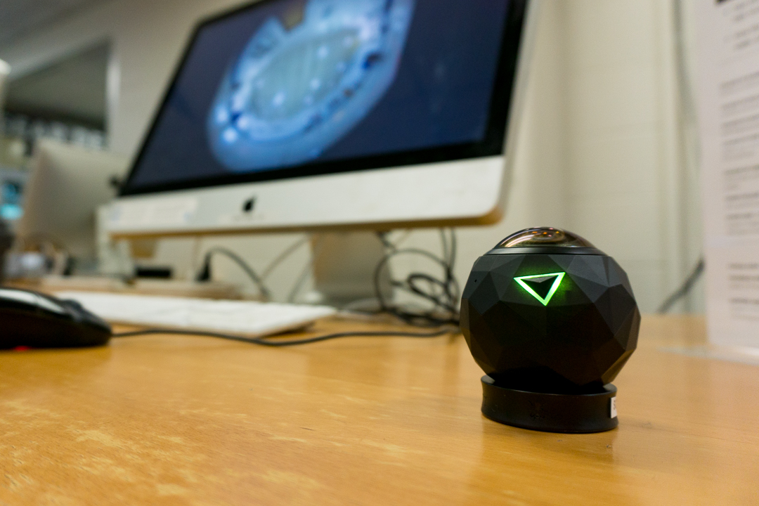 photo of 360Fly spherical camera in foreground and Apple iMac computer out of focus in background