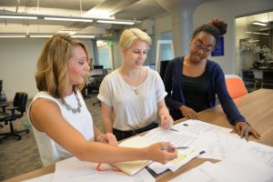 three students working on creative documents at a marketing agency