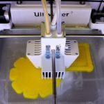 photo from front top of Ultimaker 3 printing a yellow object
