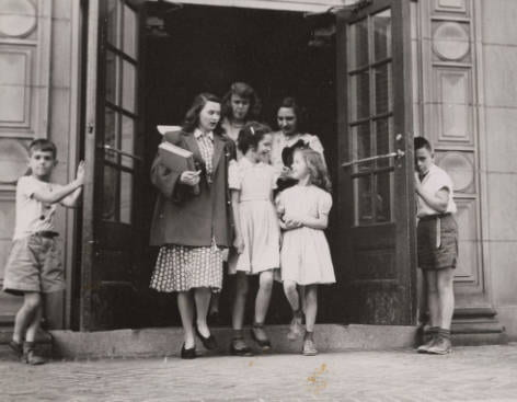 Photograph of students walking out of the campus elementary school, the present-day Van Bokkelen Hall