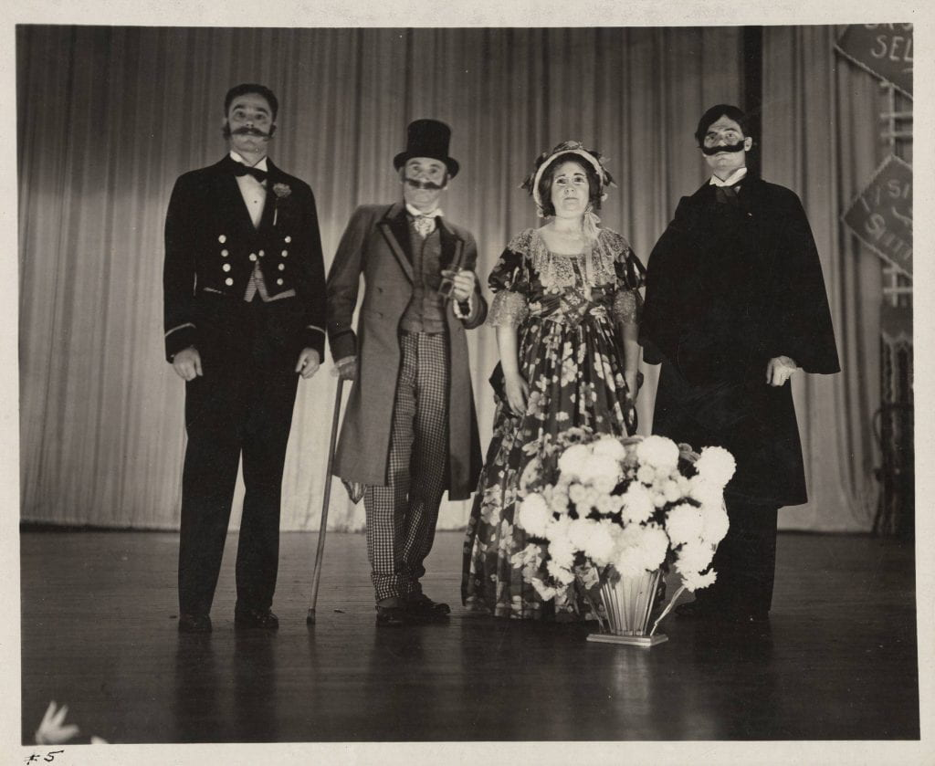From l-r: Joe West, Science teacher, as Richard Blair; Curt Walther, Geography and Social Studies professor, as The Baron of Amusement; M. Theresa Wiedefeld as perhaps Mlle. Zara; and Compton Crook, Biology professor as the villain, Egbert Van Horn.
