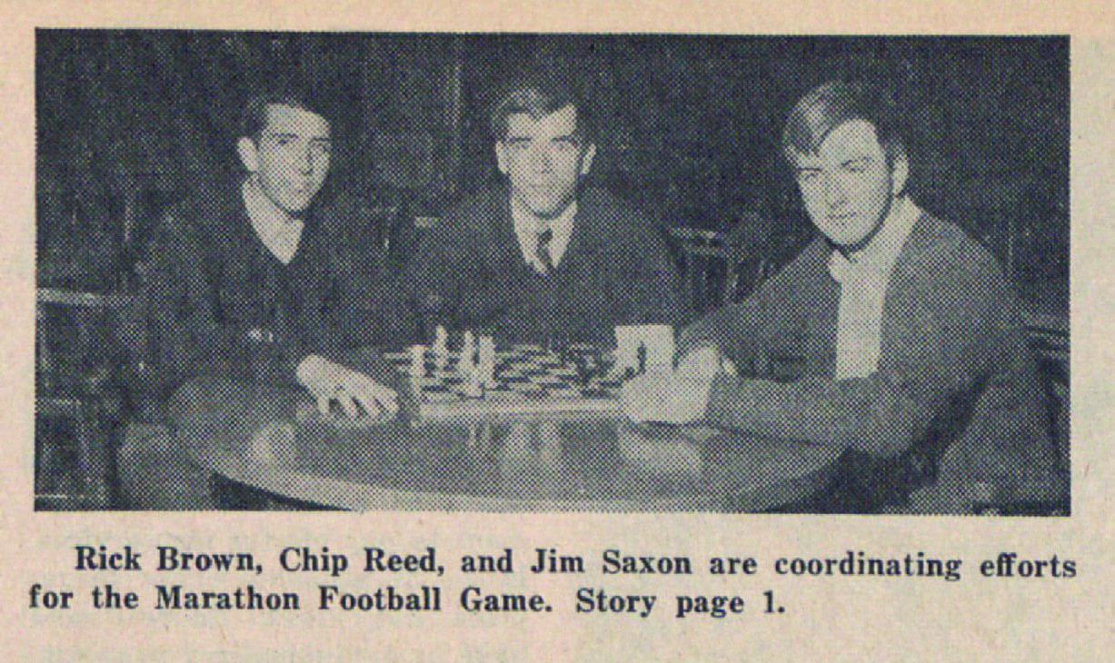 Photograph of three men gathered around a table playing chess. The caption reads Rick Brown, Chip Reed, and Jim Saxon are coordinating efforts for the Marathon Football Game.