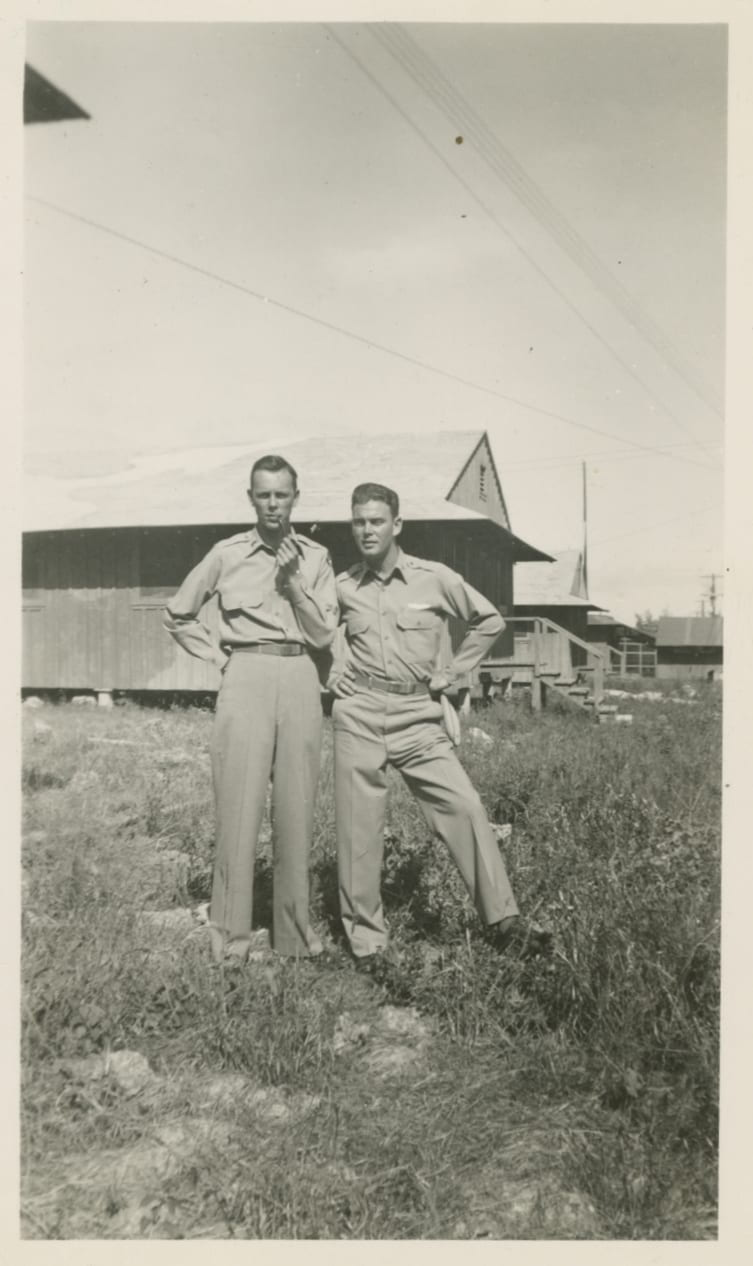 Photo of two men in uniform standing outside military barracks style buildings.