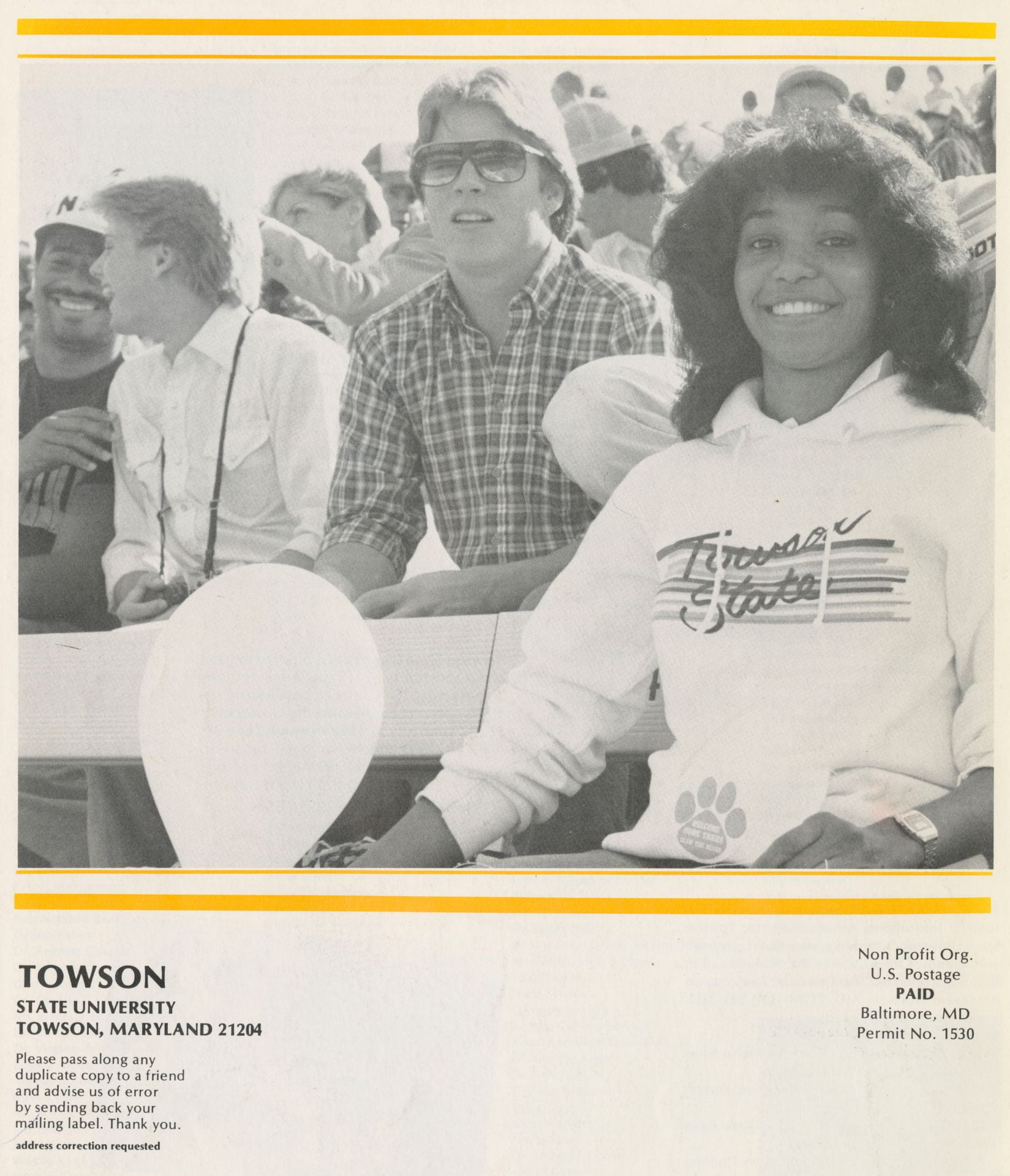 "Photo of people sitting on bleachers. One woman is wearing a sweatshirt that says ""Towson State"""