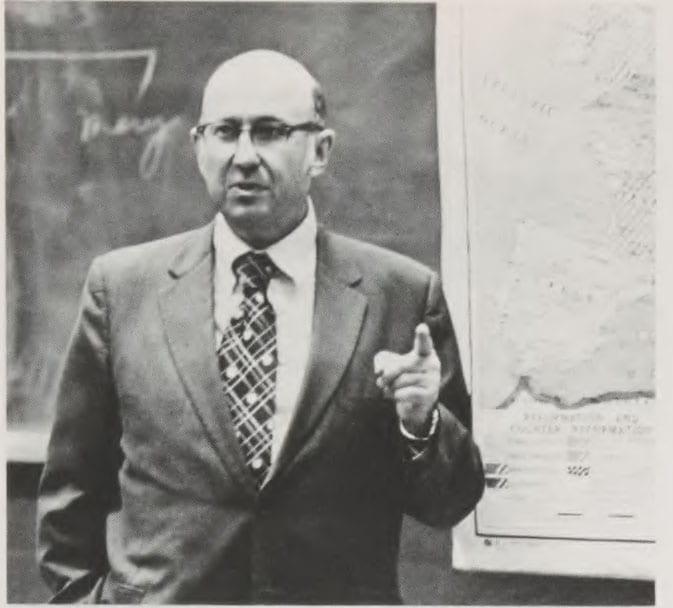Blumberg standing in front of chalkboard teaching.