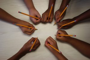 multiple students' hands arranged in a circle, each holding a pencil