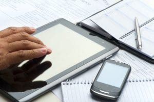 Hand typing on a digital tablet with mobile phone