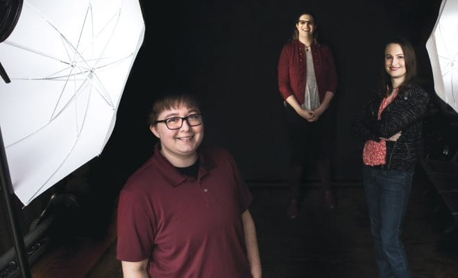 From left, James James Imperiali '13, Janelle Drake ;11, and Jolene Cotnoir '10 standing between two photographer's umbrella lights