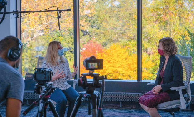 Lisa Pearlman and President Laurie Leshin seated before large windows with fall foliage visible; cameras and a cameraman are visible in the foreground