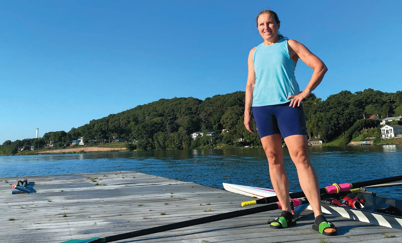 Carla Ferrara '83 standing on a dock with a crew shell and oar behind her