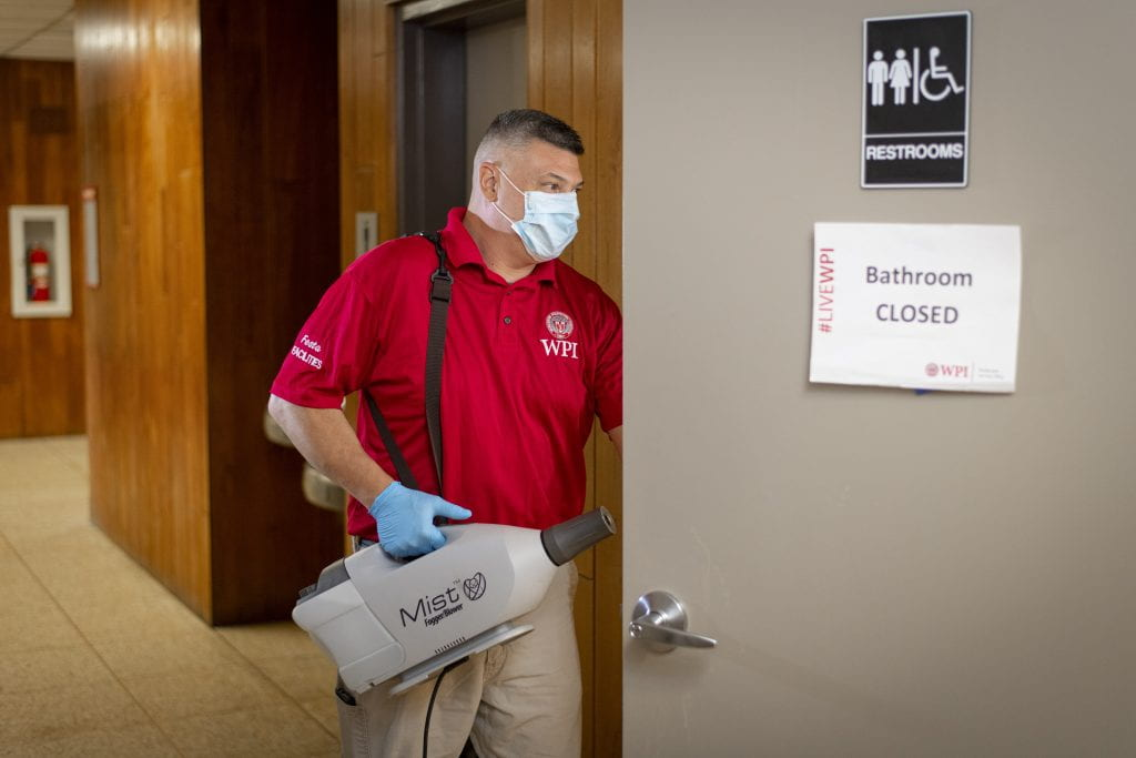 A Facilities employee enters a bathroom with a fogging device