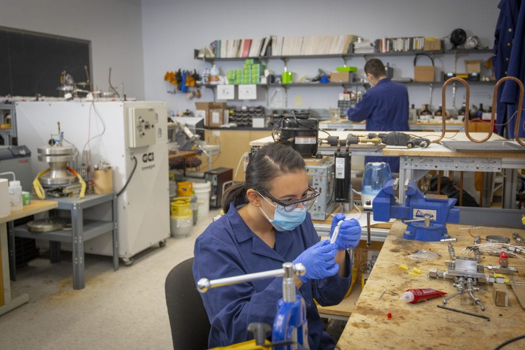 Students in a mechanical engineering lab work while wearing masks and observing social distancing