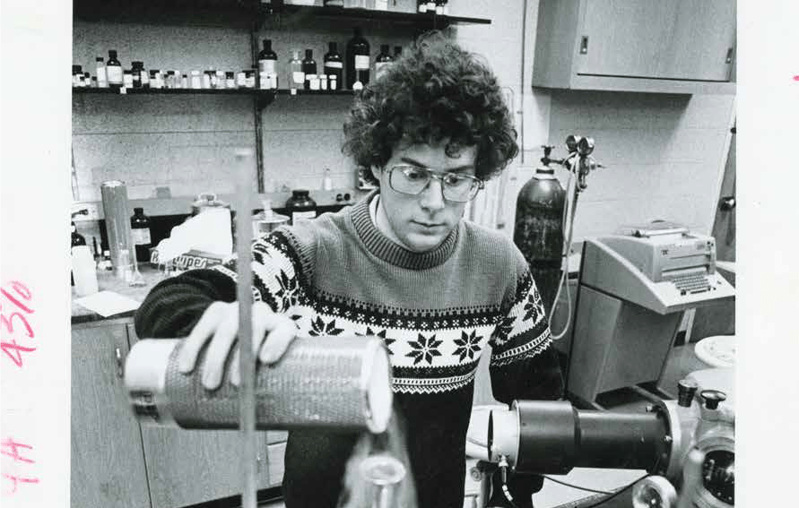 Black and white image of a student pouring liquid nitrogen into a beaker in a chemistry lab