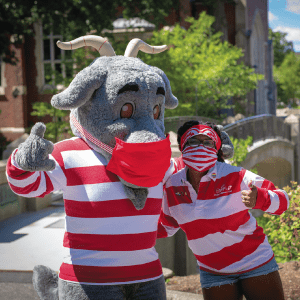 the Gompei the Goat mascot with its arm around a student; both wear red-and-white striped shirts