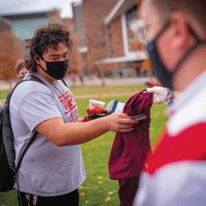 an SAS member hands a t-shirt to a student wearing a WPI t-shirt