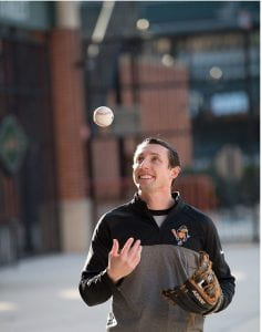 Joseph Botehlo in an Orioles shirt tosses a baseball in the air