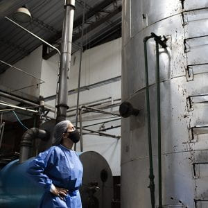 Leila Carvajal Erker, in blue coveralls and a black face mask, stands before a tall silver tank in a factory