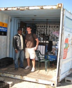 Project team member, Mike Fitzpatrick, poses with a cell phone service and repair shop owner in C section, Monwabisi Park.