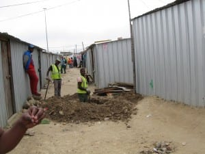 Workers lay pipes in Mtshini Wam to add toilets to nearly every home in Mtshini Wam