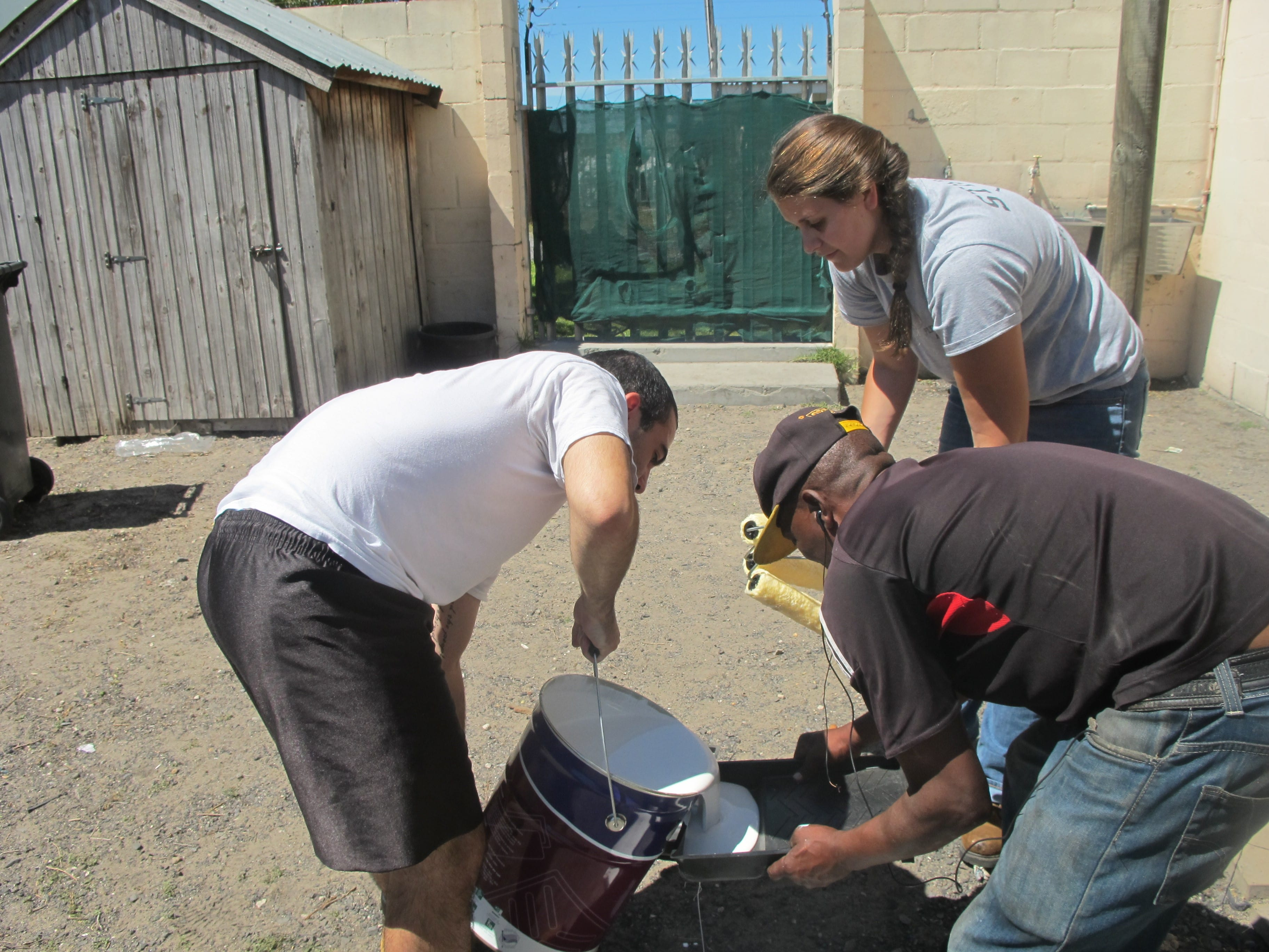 Chrissy, Jon, and Golden work together to keep the paint trays filled so painting can continue