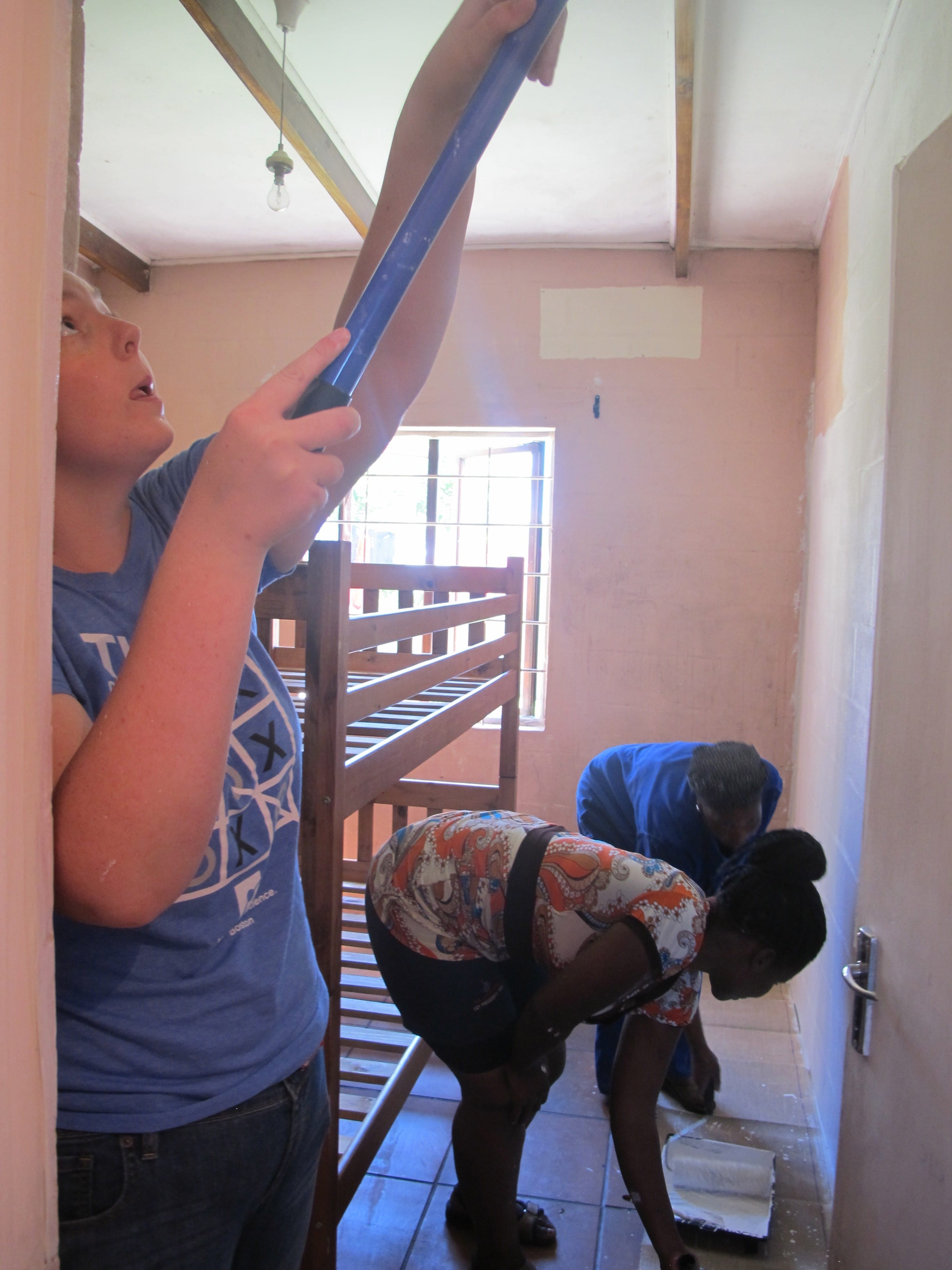 Julia works with two of the community women to paint one of the bedrooms