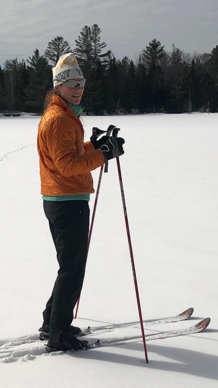 Becky Sutter skiing on a frozen Adirondack lake with orange jacket, white hat, and sunglasses
