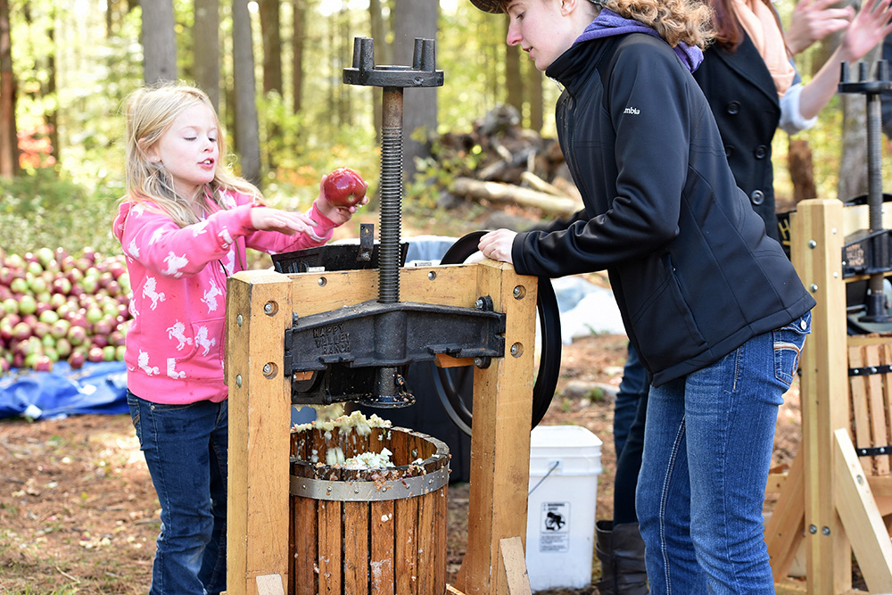 A young girl making cider.