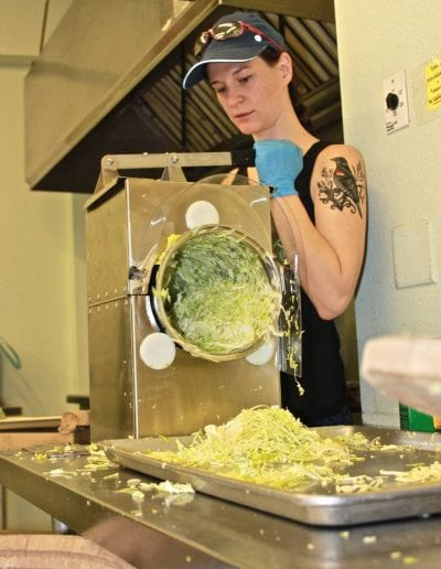 Dr. Eidem shredding cabbage to let microbes do their fermentation work and make delicious sauerkraut.
